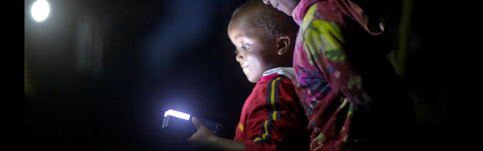 Child looking at a glowing mobile device in the dark