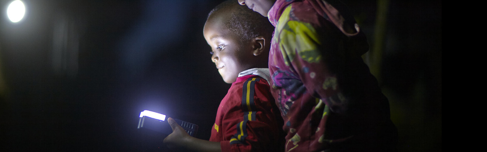 a child looking at a glowing handheld device in the dark