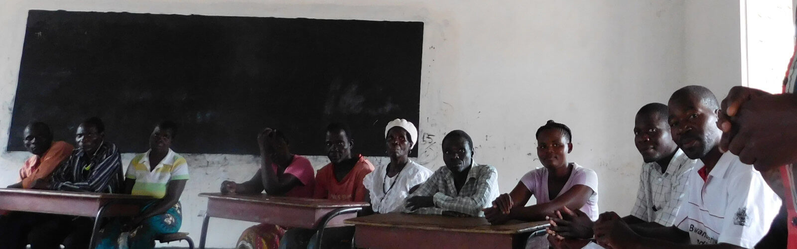 A group of adults sitting on desks in a classroom in front of a blackboard