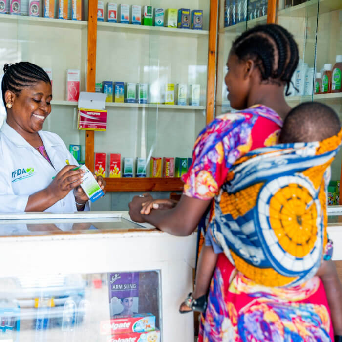 A mother and her child talk with a pharmacist at an Accredited Drug Dispensing Outlet (ADDO) in Tanzania