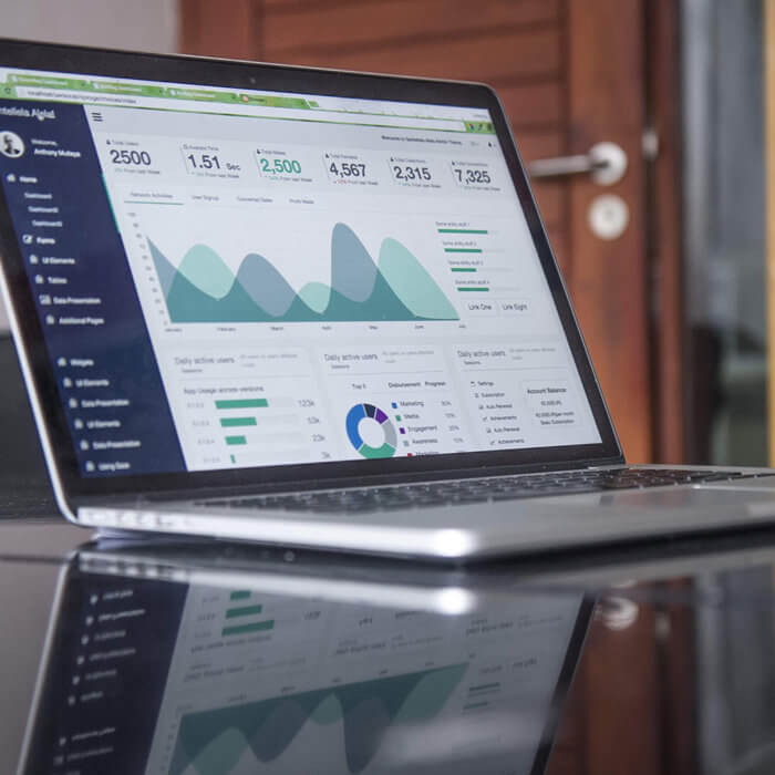a laptop showing charts and graphs on screen