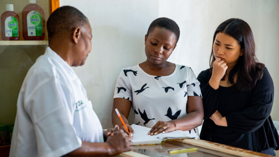 The R4D Tanzania team visits an ADDO pharmacy in Dar es Salaam, where pharamacy owner Ester Shoo and staff member Esther Andrews consult with patients and record drug stocks in their franchise.